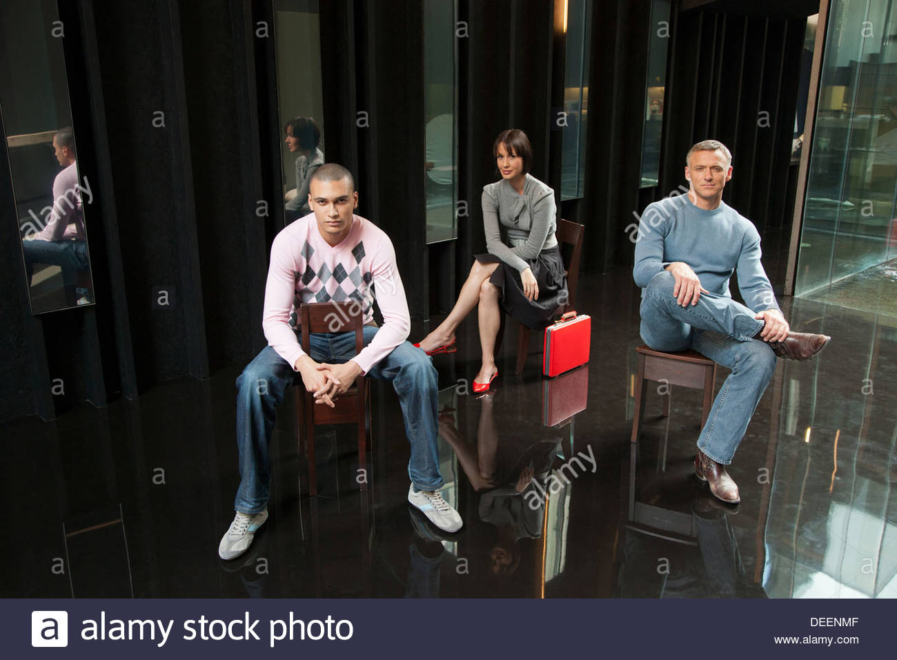 Three businesspeople sitting in an office - Stock Image