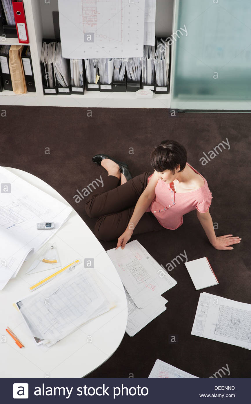 Businesswoman looking at paperwork on the floor - Stock Image