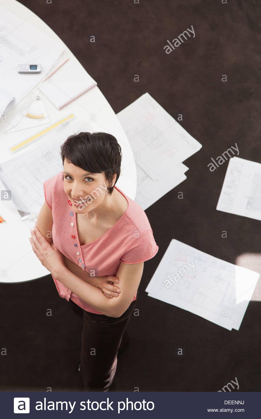 Businesswoman looking up with paperwork on floor - Stock Image
