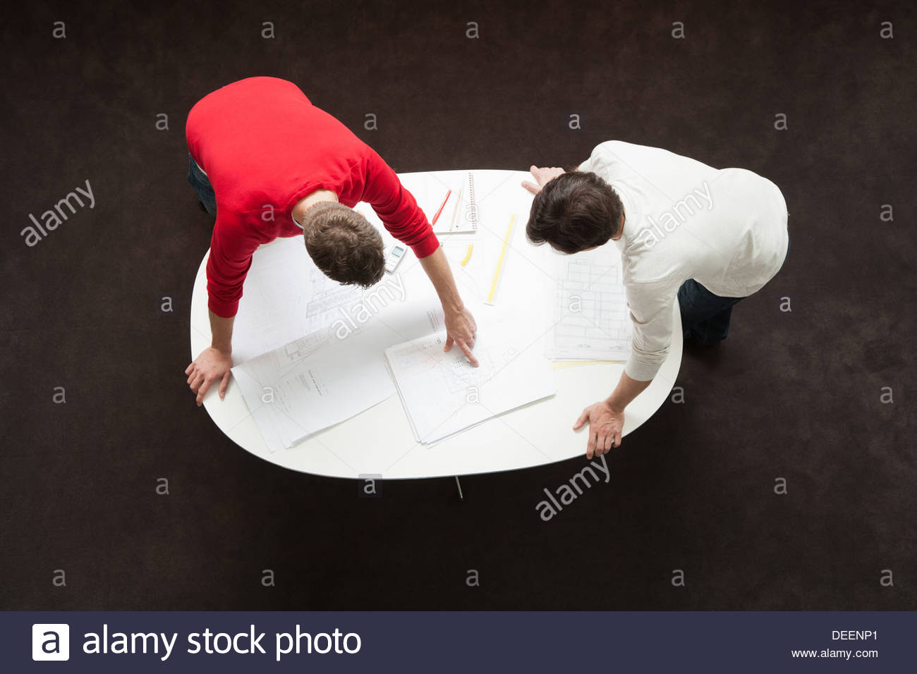 Two businessmen leaning over a table with drafts and paperwork - Stock Image