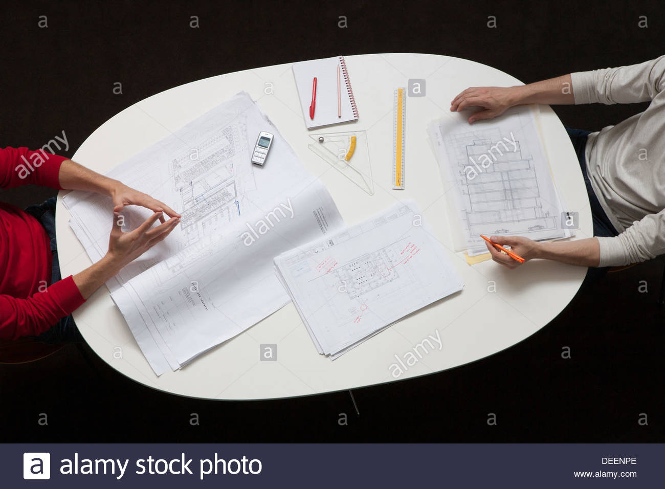 Two businessmen at a table with drafts and paperwork - Stock Image