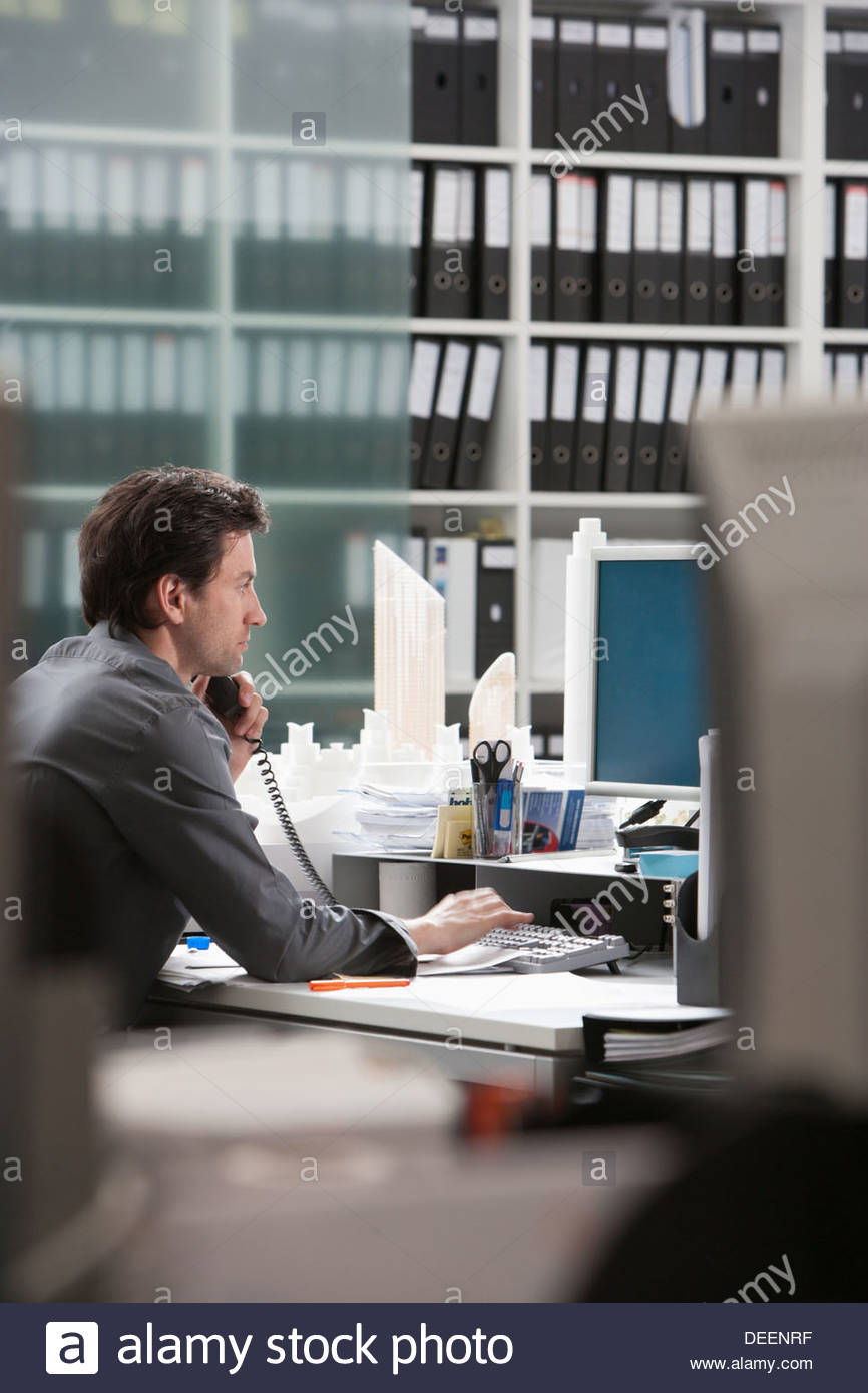 Businessman on telephone at desk in office - Stock Image