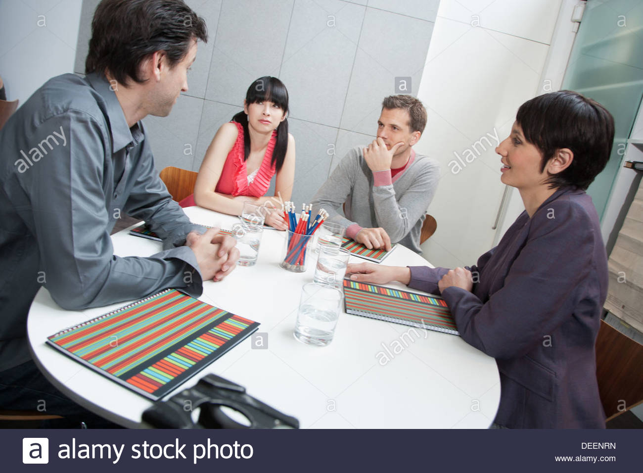 Four businesspeople in an office - Stock Image