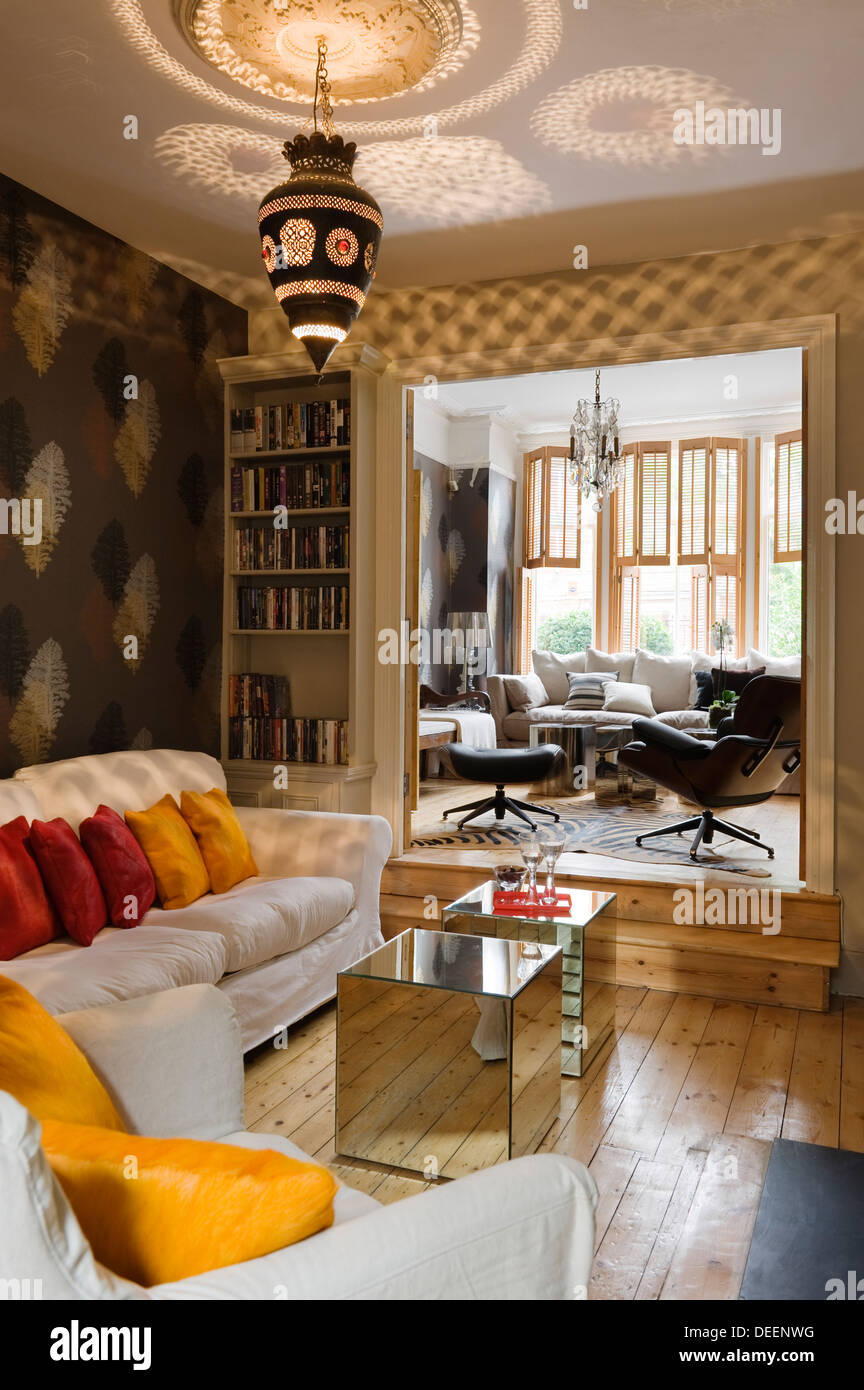 Living area with mirrored Armada cubes, a Moroccan lantern and silk cushions of warm spice tones - Stock Image