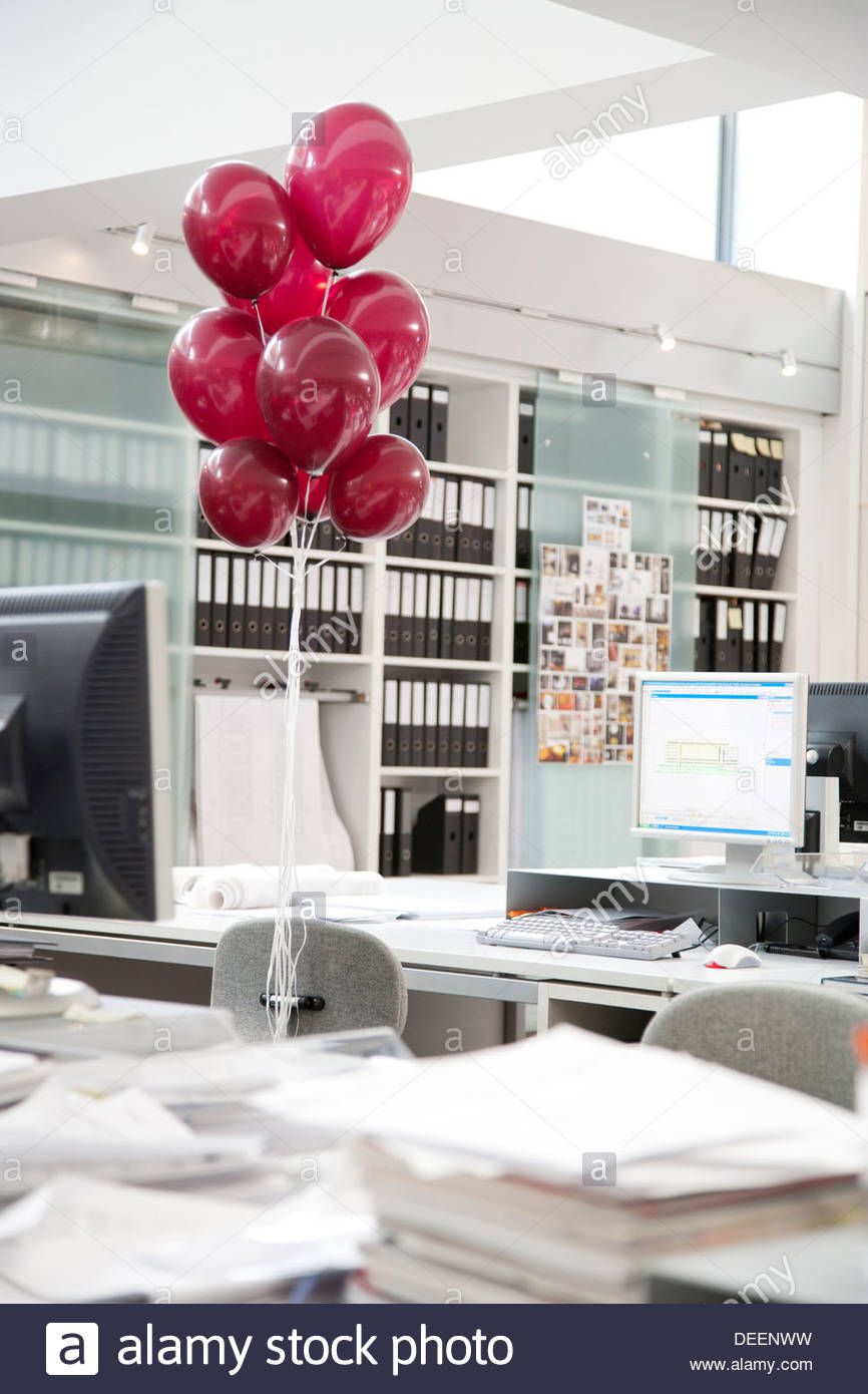 Empty desk with red balloons tied to chair - Stock Image