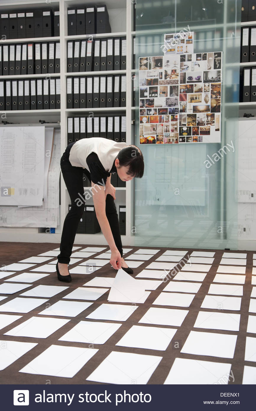 Businesswoman picking a piece of paper on the floor - Stock Image