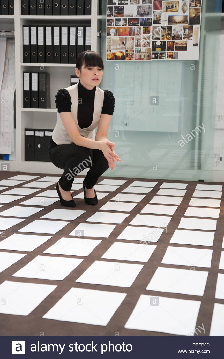 Businesswoman crouching on a floor - Stock Image