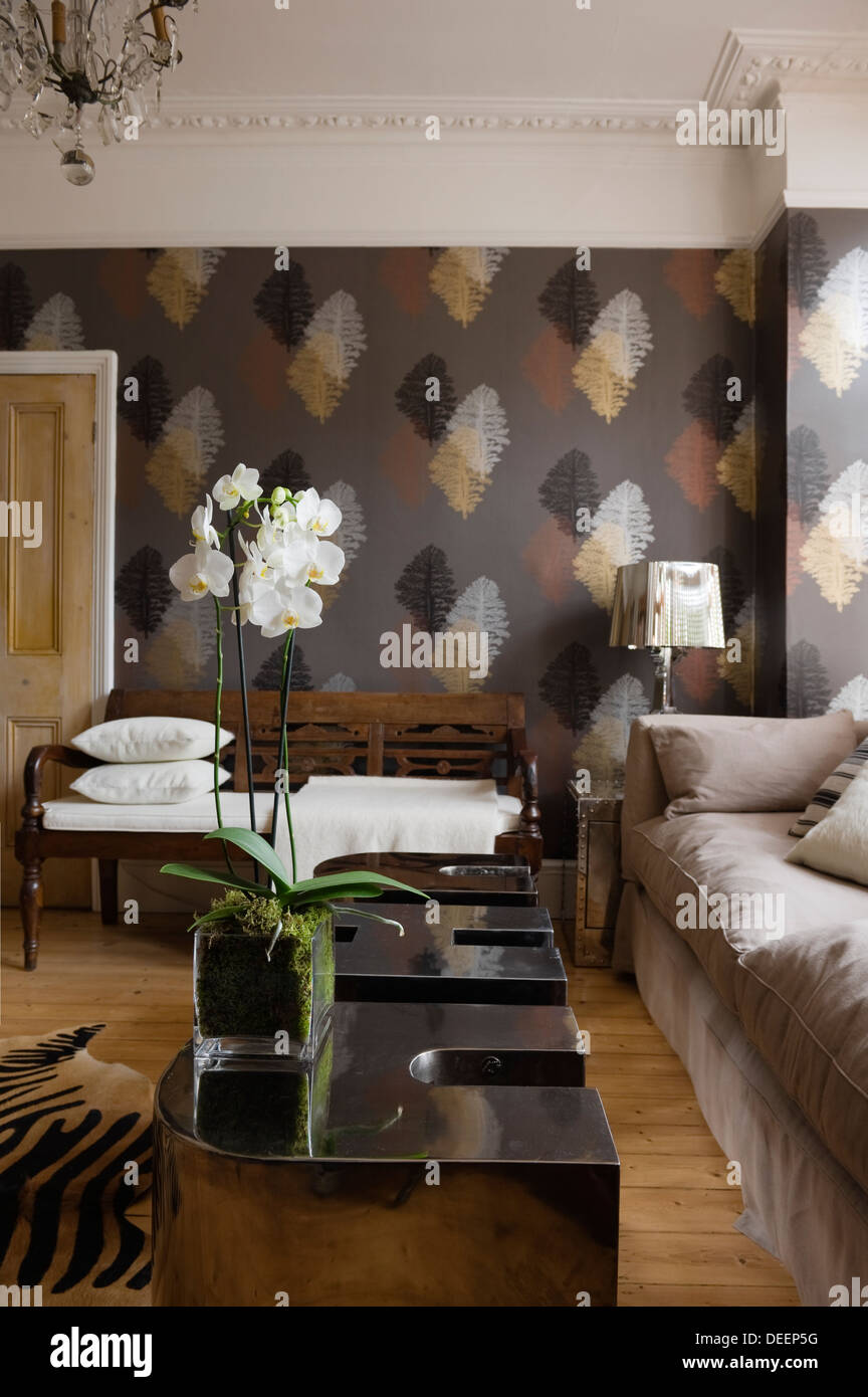 Leaf motif wallpaper with metallic accents in eclectically furnished living area - Stock Image