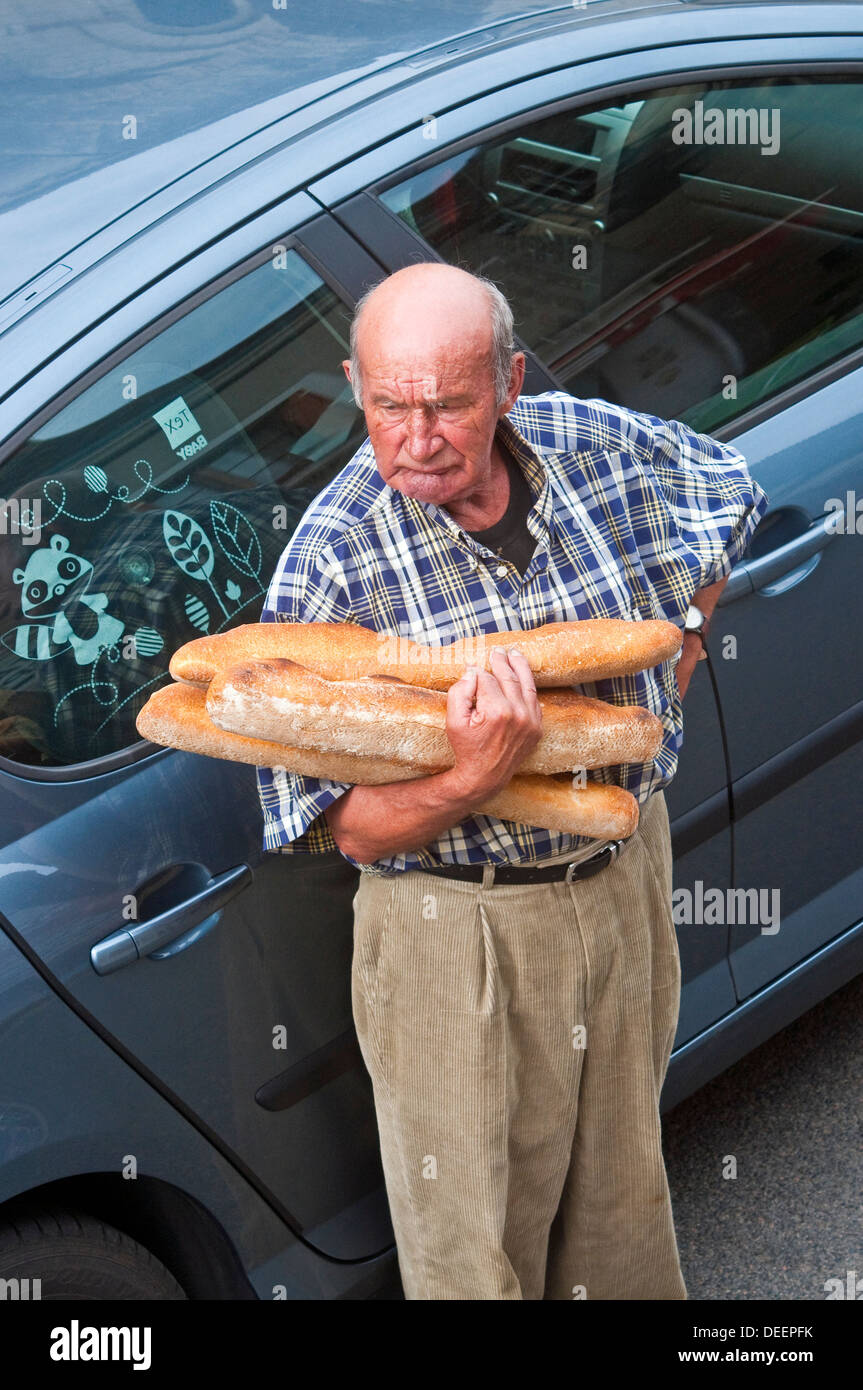 Frenchman holding his daily bread - France. - Stock Image