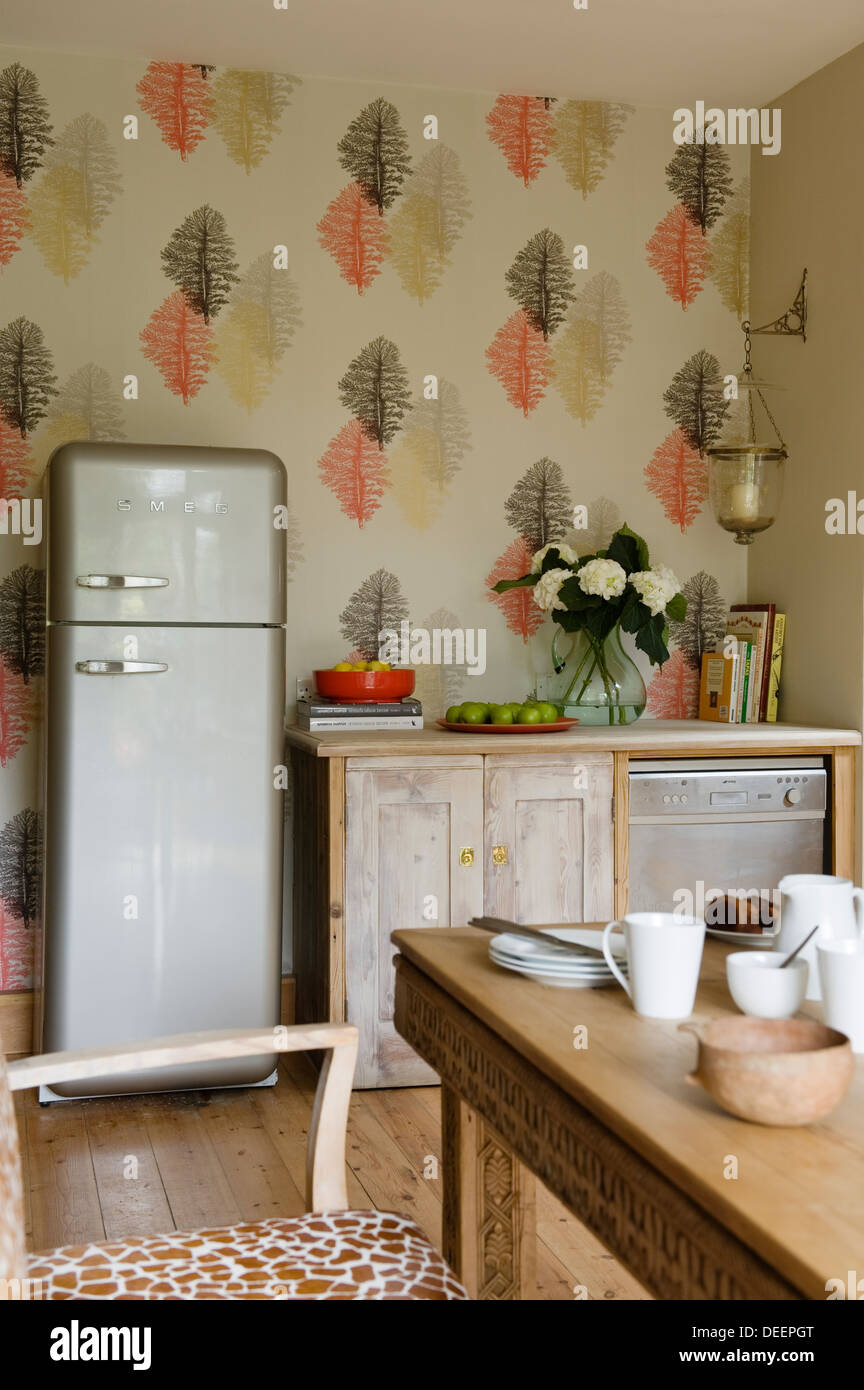 Vintage kitchen with Fornasetti designed wallpaper and retro fridge - Stock Image