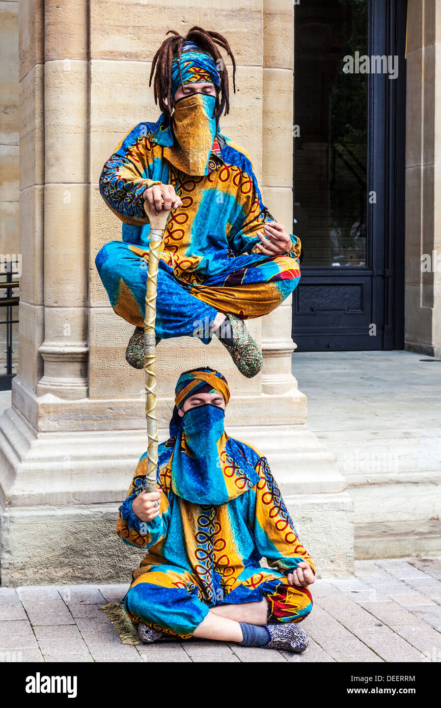 Two street entertainers performing a levitation trick in the Place d'Armes, Luxembourg City. - Stock Image