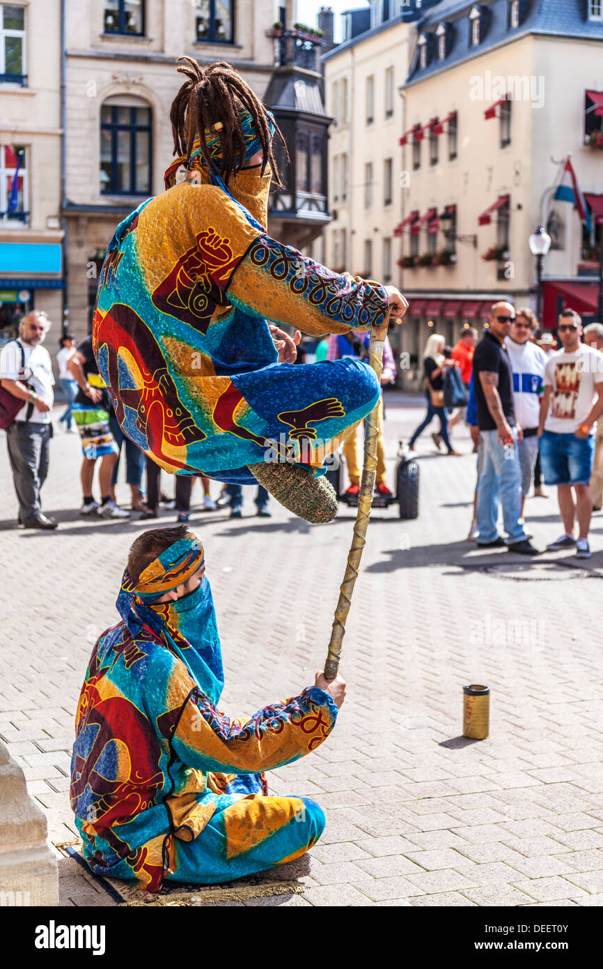 Tourists watching two street entertainers performing a levitation trick in the Place d'Armes, Luxembourg City. - Stock Image