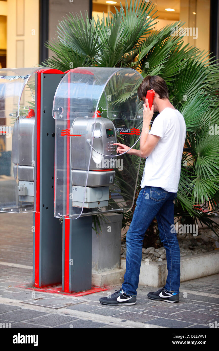 A man using a Telecom Italia payphone in Pescara, Italy. - Stock Image