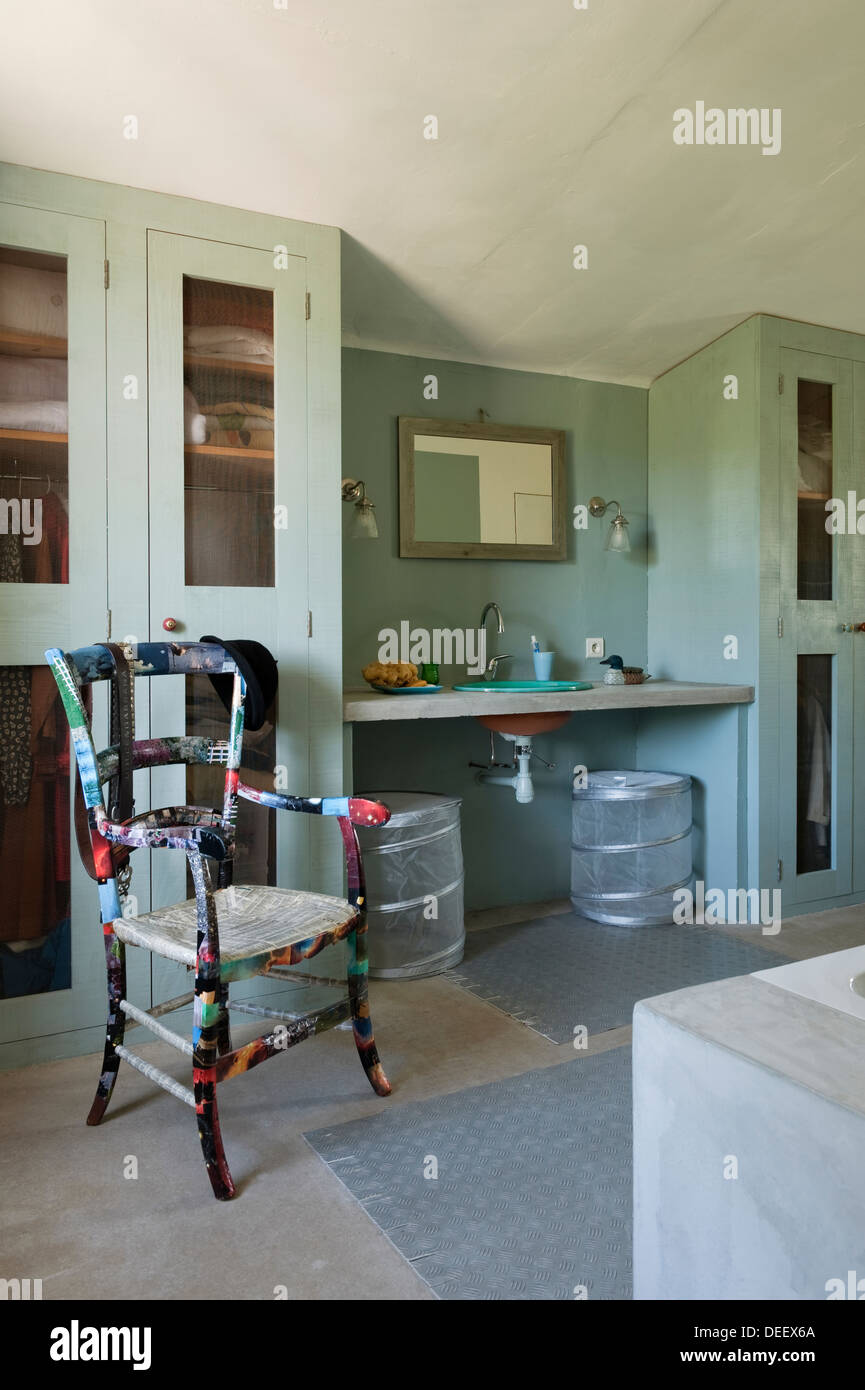 Bathroom storage and concrete vanity top and hand basin with rejuvenated old chair varnished for a durable finish - Stock Image