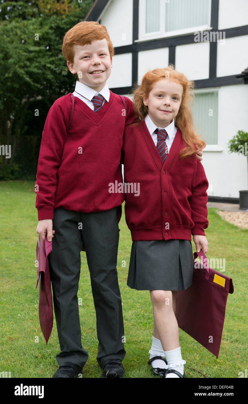 Brother and sister in their school uniform outside their home. - Stock Image