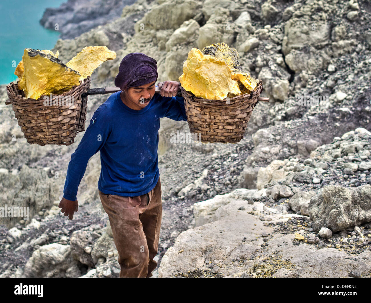 Sulfur miner carrying load of solid sulfur at the Kawah Ijen volcano in Indonesia. - Stock Image