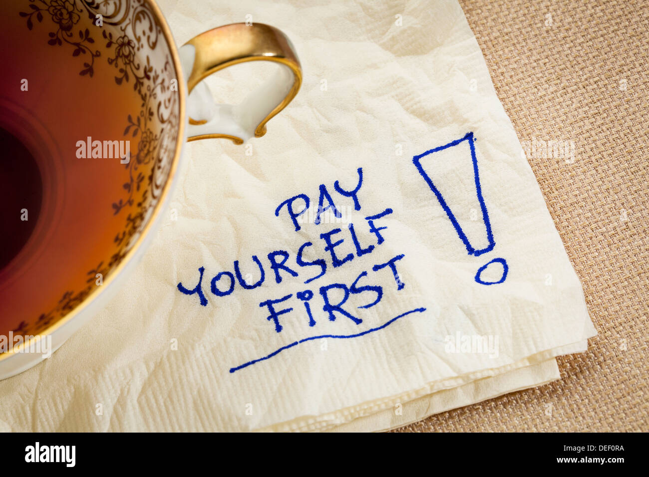 pay yourself first, a reminder of personal finance strategy - a napkin doodle with a tea cup - Stock Image