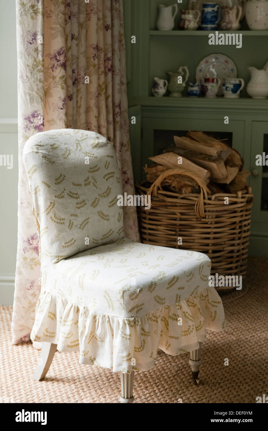 Country house upholstered chair and firewood - Stock Image