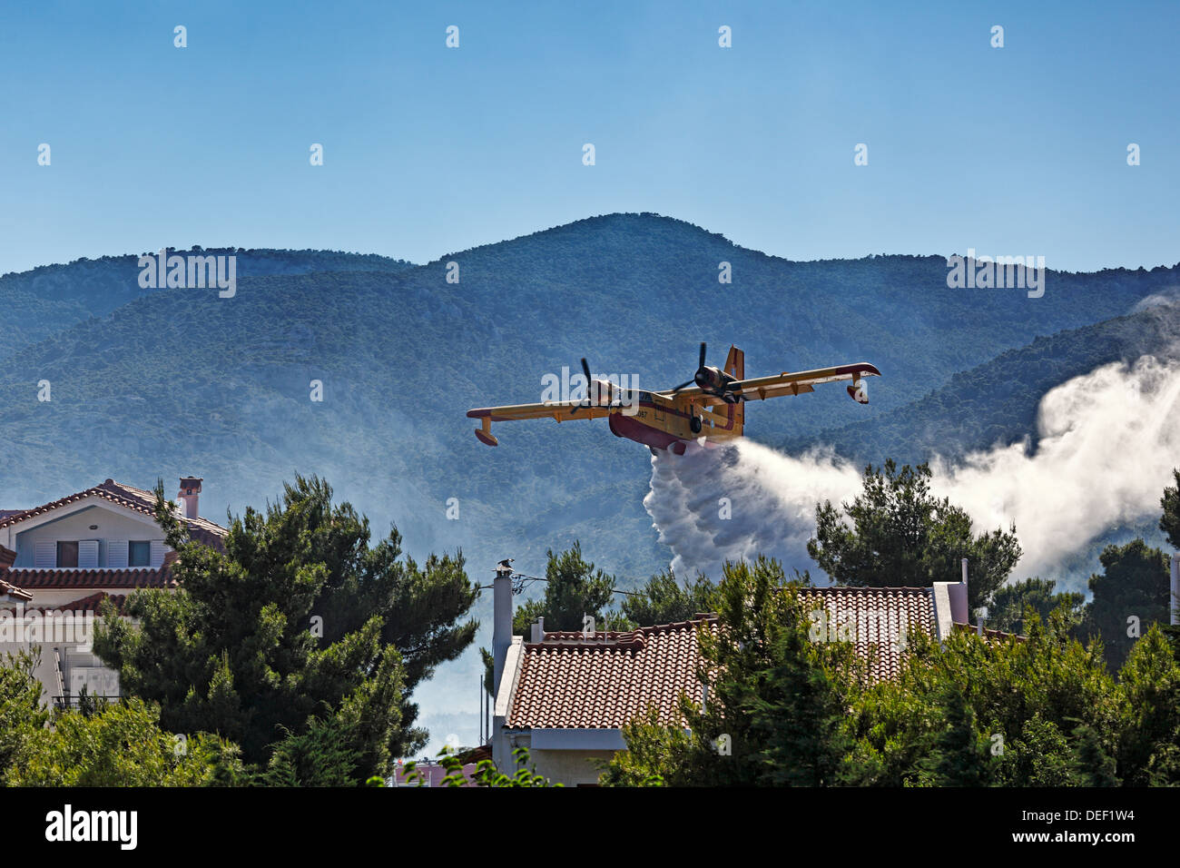A fire fighting plane extinguished the fire over houses - Stock Image