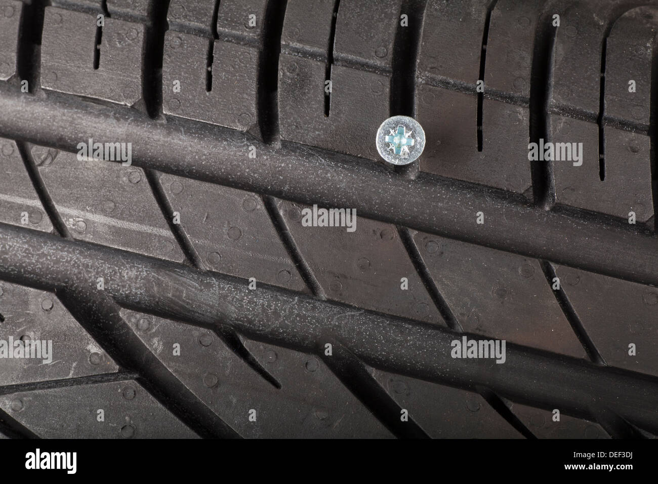Nail, Screw in a brand new tyre, puncture - Stock Image