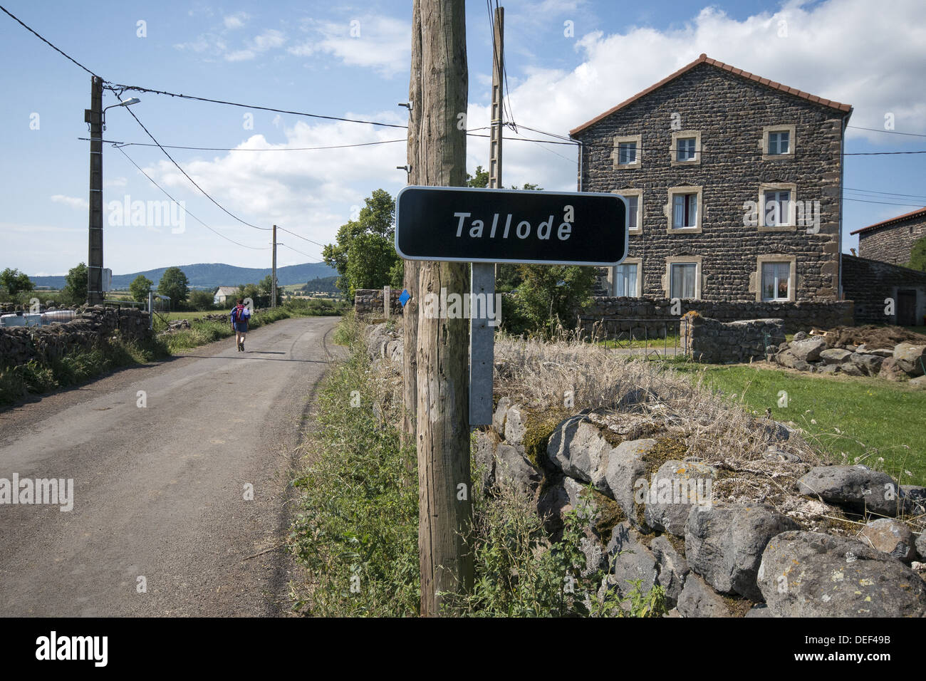 Pilgrim walking through the small village of Tallode on the GR65 walking route the Way of St James in France - Stock Image