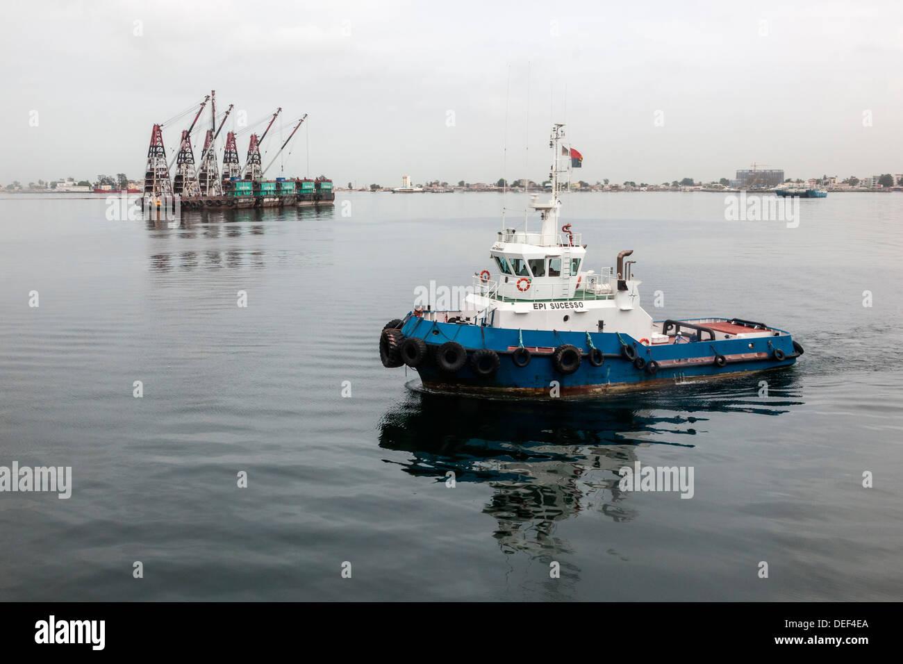 Africa, Angola, Luanda. Tug boat near barge. - Stock Image