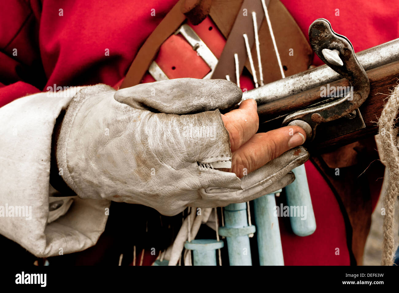 Hand of man in period costume holding matchlock musket - Stock Image