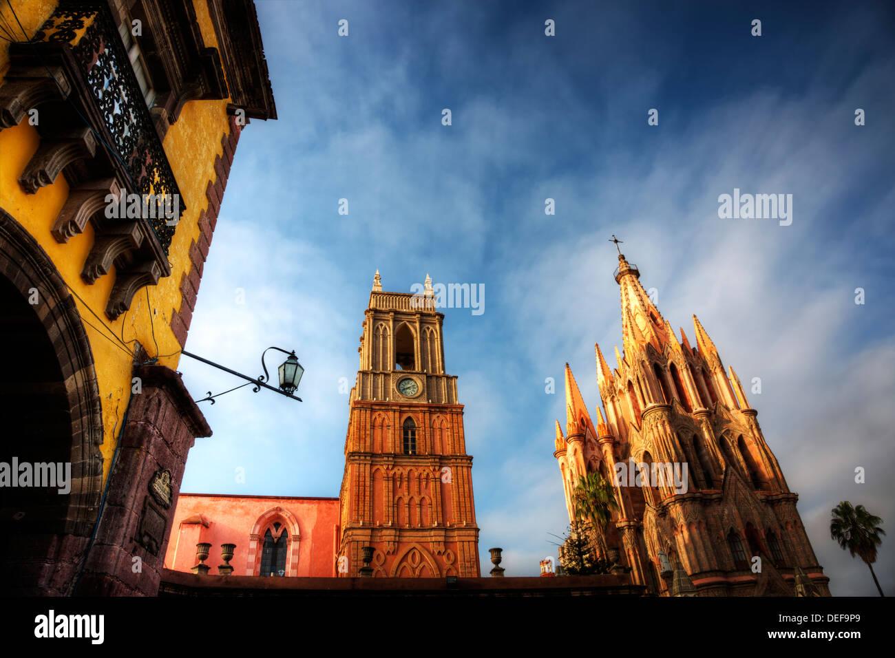 The morning sun illuminates the spires of the Parroquia de San Migulel Arcangel. - Stock Image