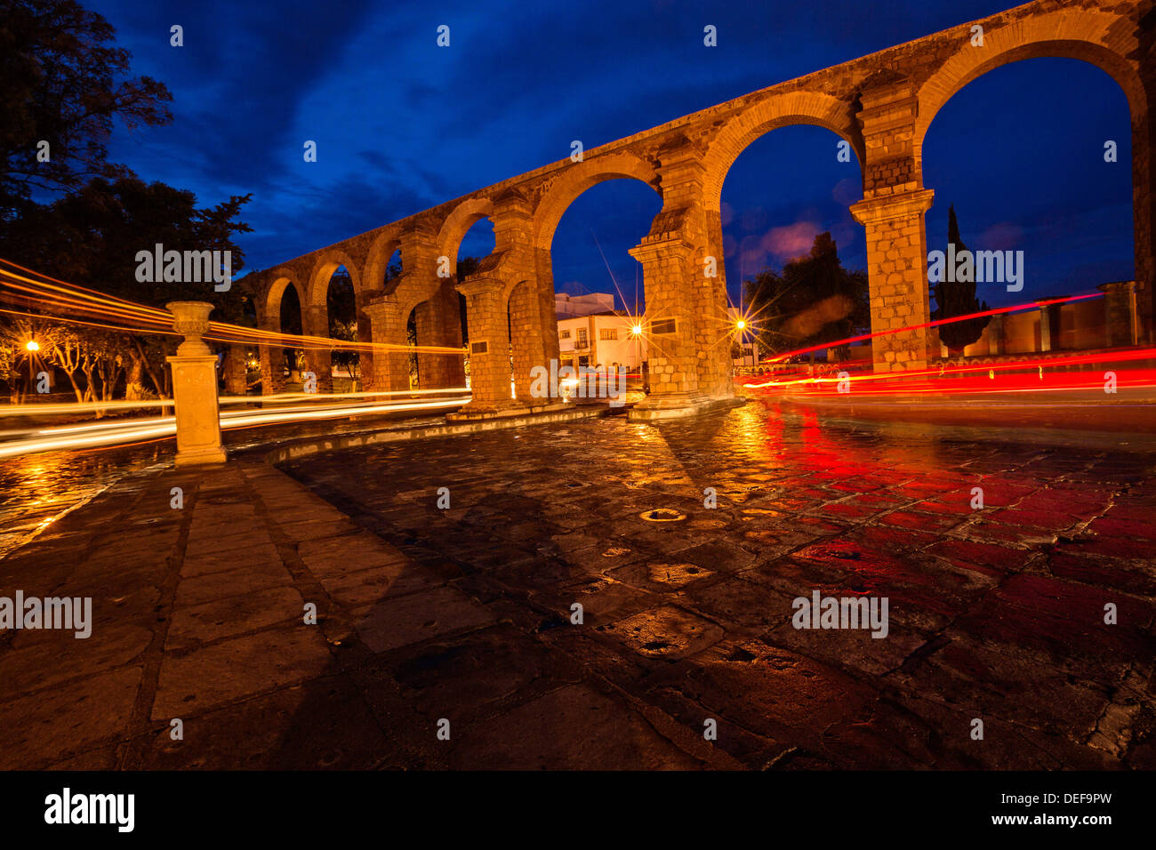 The remains of the El Cubo aqueduct in Zacatecas, Mexico, at night after a rain storm. - Stock Image