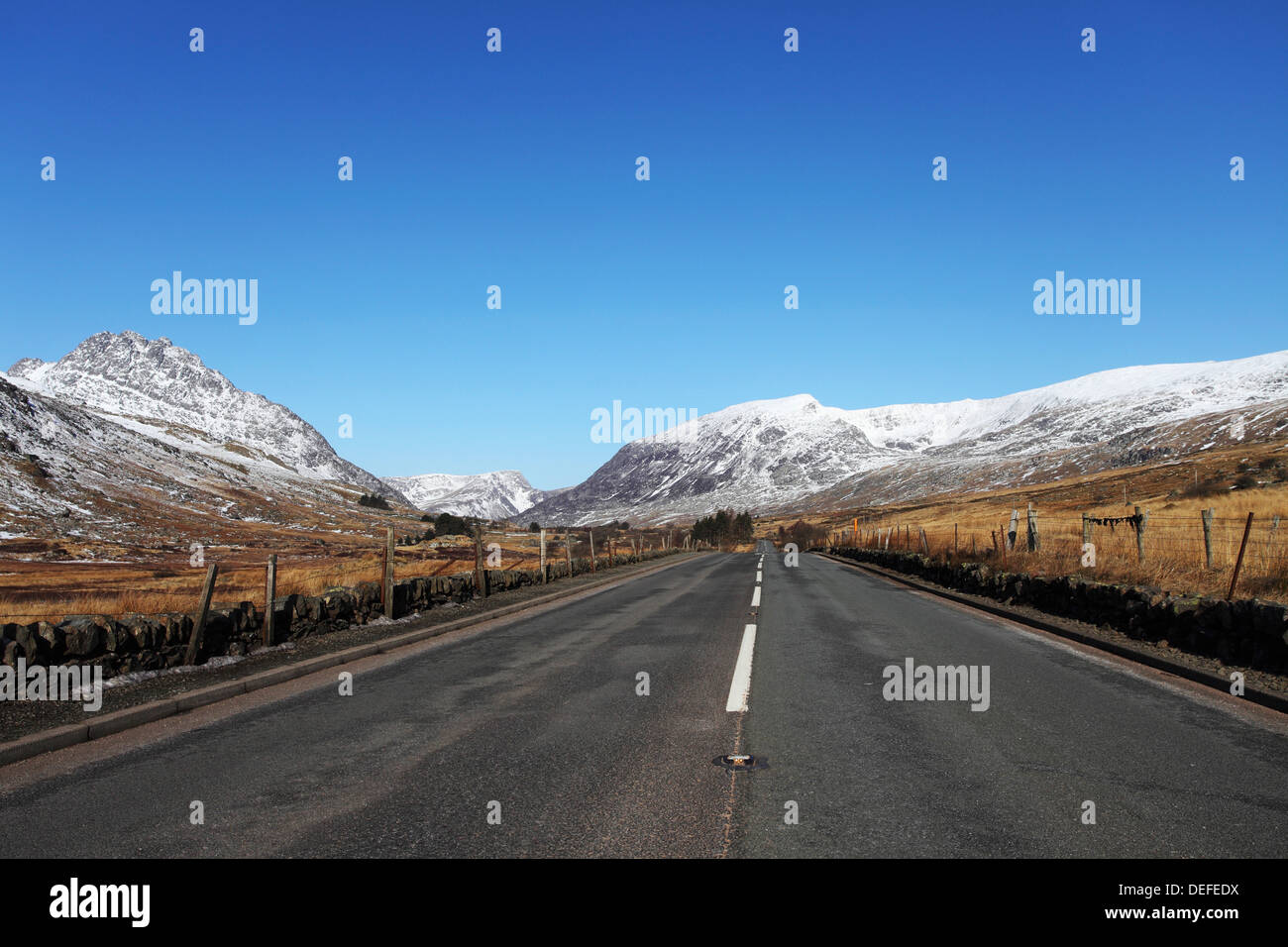 The A5 road runs through past snow-capped mountains in Snowdonia National Park, Wales, United Kingdom, Europe - Stock Image