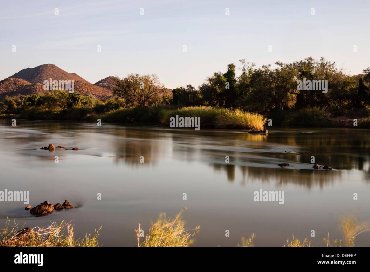 View over the border river of Kunene towards Angola, Kaokoland, Kunene Region, Namibia - Stock Image