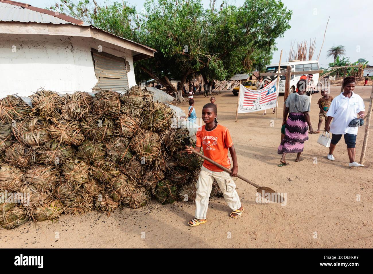 Africa, Liberia, Monrovia. People walking by bundles of dried pandanus. - Stock Image