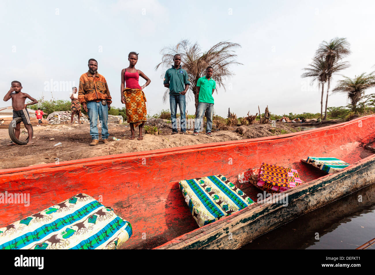 Africa, Liberia, Monrovia. People gathered by traditional pirogue boat on the Du River. - Stock Image