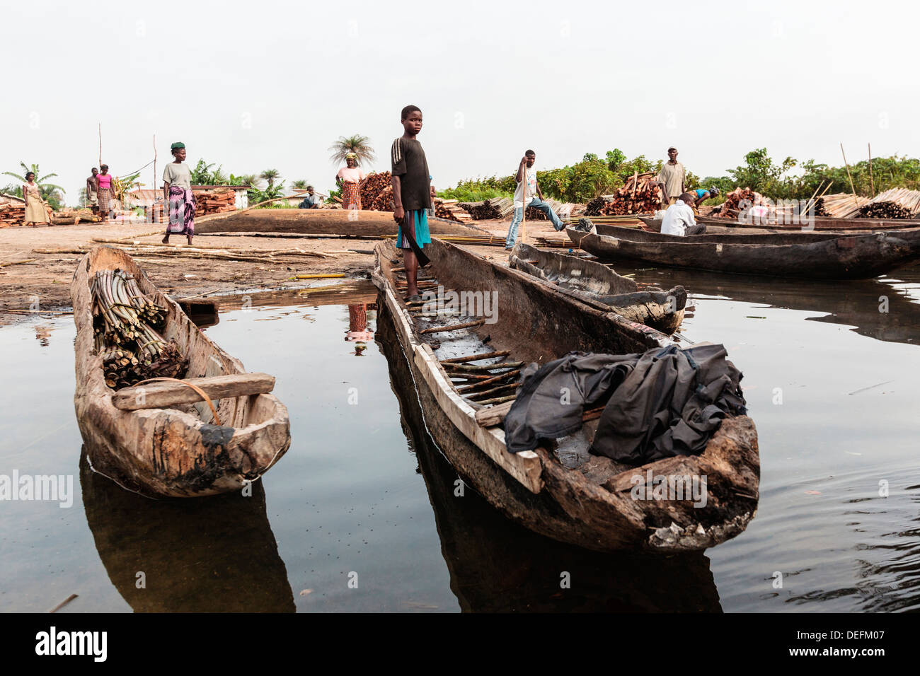 Africa, Liberia, Monrovia. People gathered by traditional pirogue boats on the Du River. - Stock Image