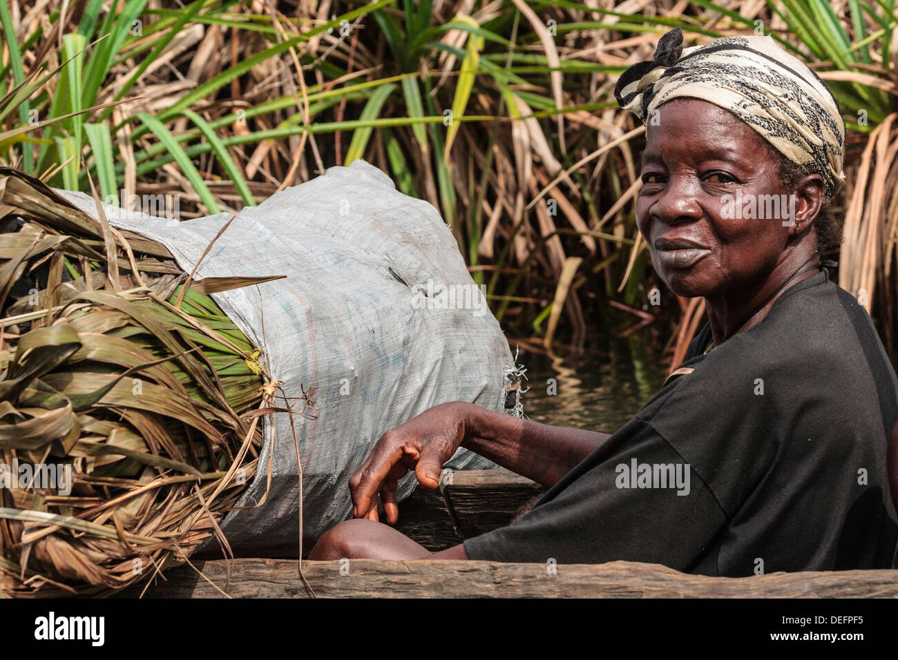 Africa, Liberia, Monrovia. Woman in traditional pirogue moving down Du River. Stock Photo