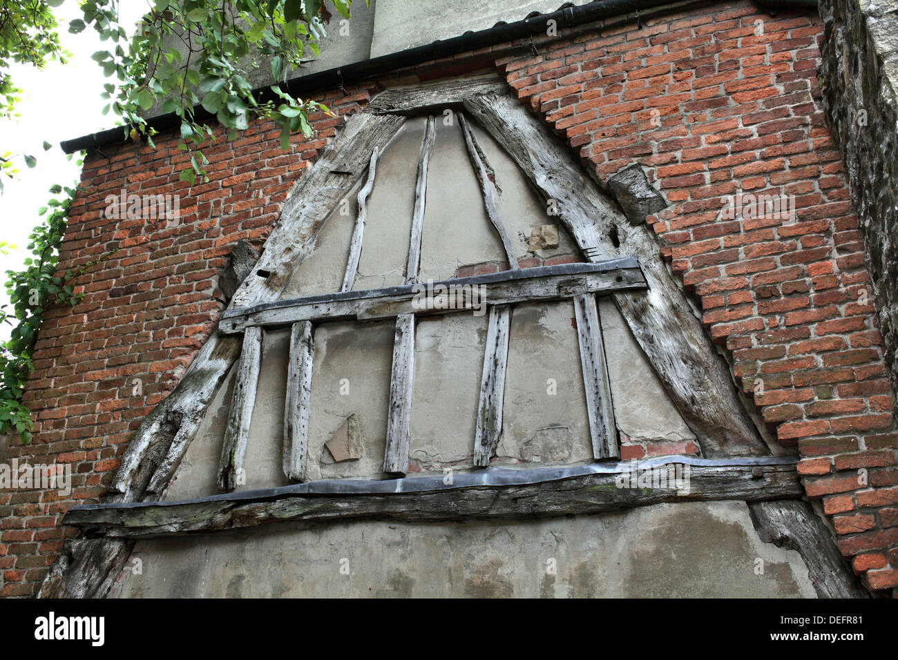 A wooden cruck remaining from the demolition of an old medieval building, High Street, Wirksworth, Derbyshire. - Stock Image