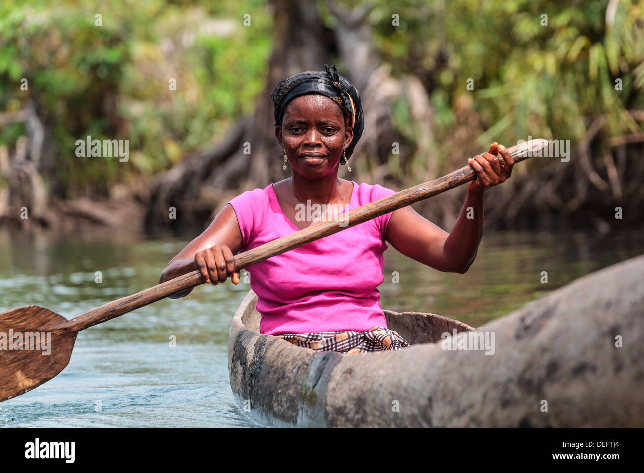 Africa, Liberia, Monrovia. Woman rowing traditional pirogue down Du River. - Stock Image