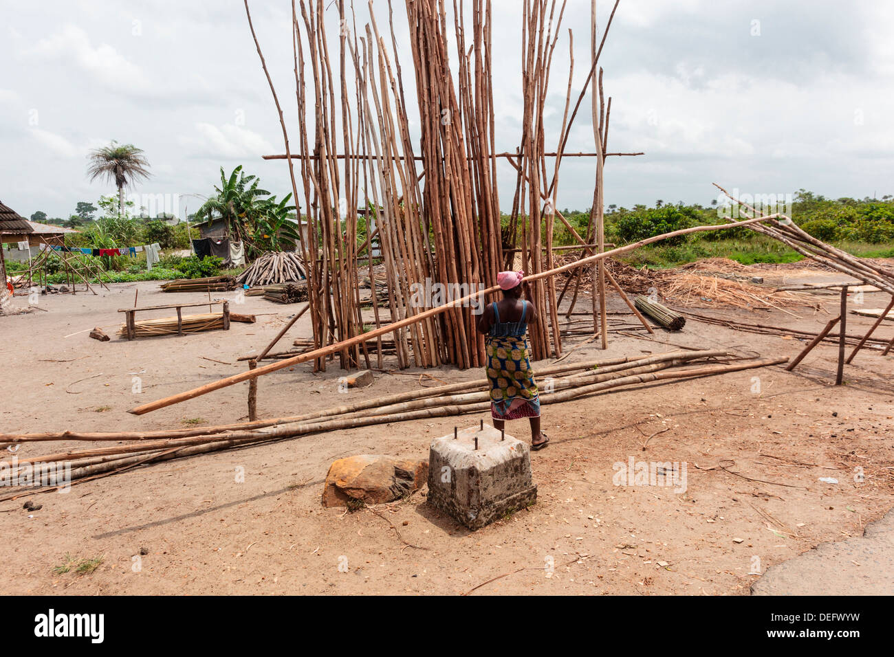 Africa, Liberia, Monrovia. Woman lifting wood to use as structure for house. - Stock Image