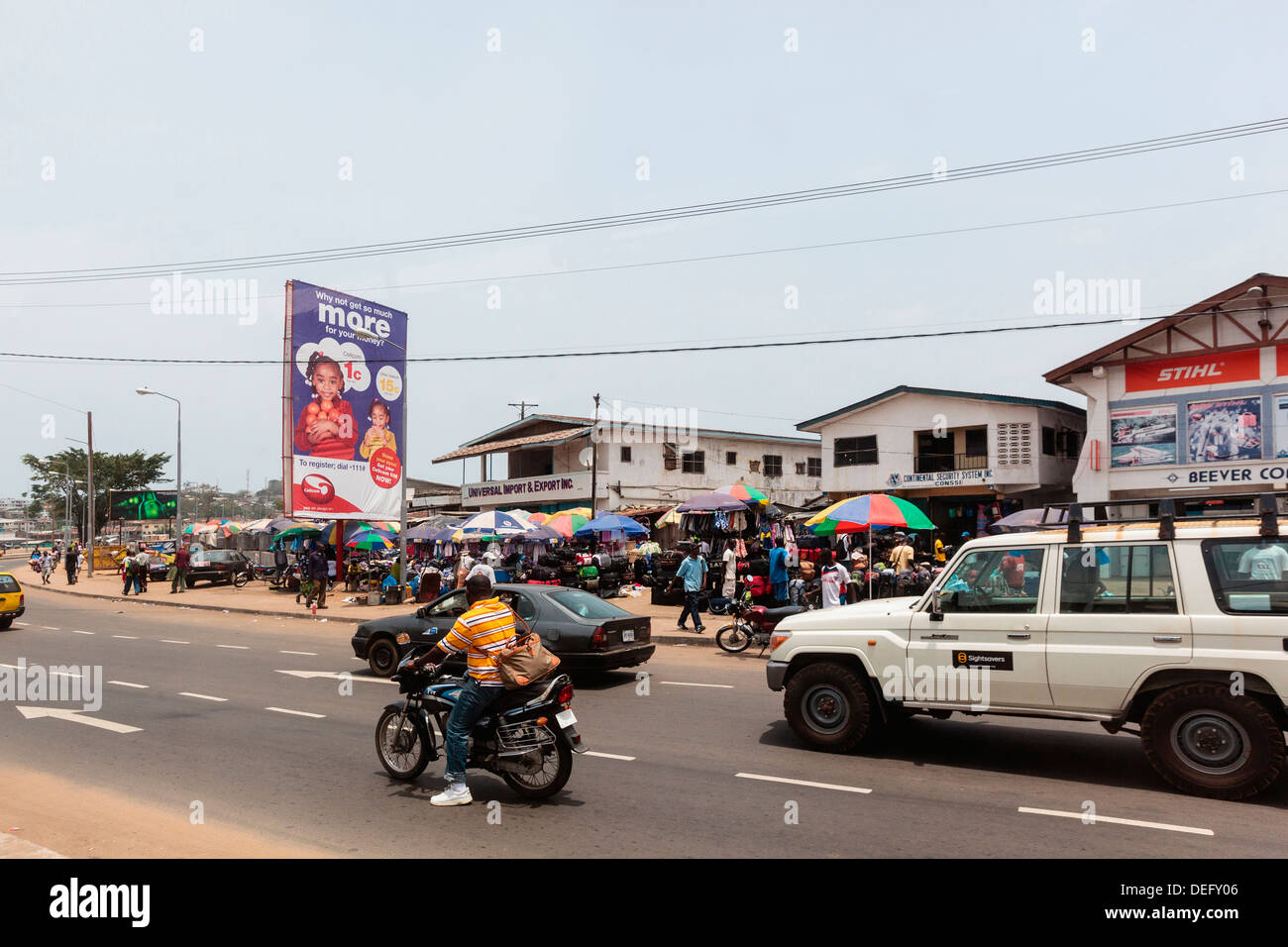 Africa, Liberia, Monrovia. Traffic rushing by busy city market. - Stock Image