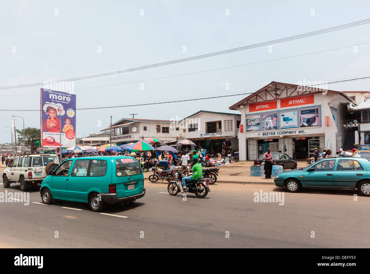 Africa, Liberia, Monrovia. Traffic rushing by busy city market. Stock Photo