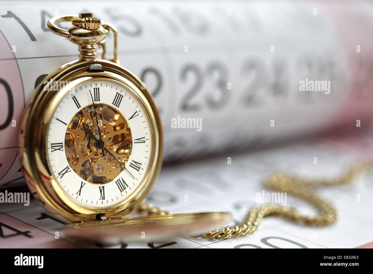 Gold pocket watch and calendar - Stock Image