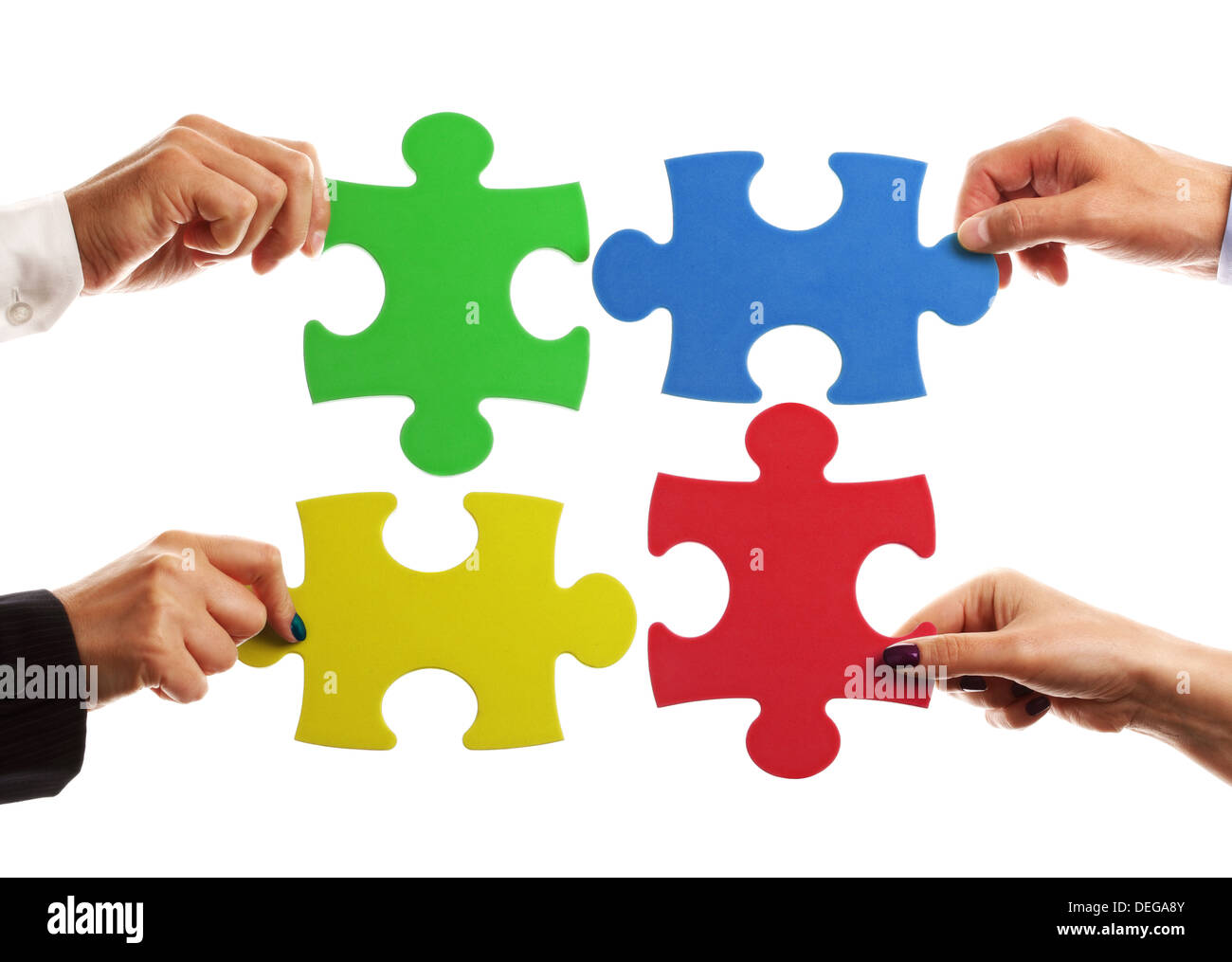Teamwork strategy or partnership concept with business team holding jigsaw pieces together - Stock Image