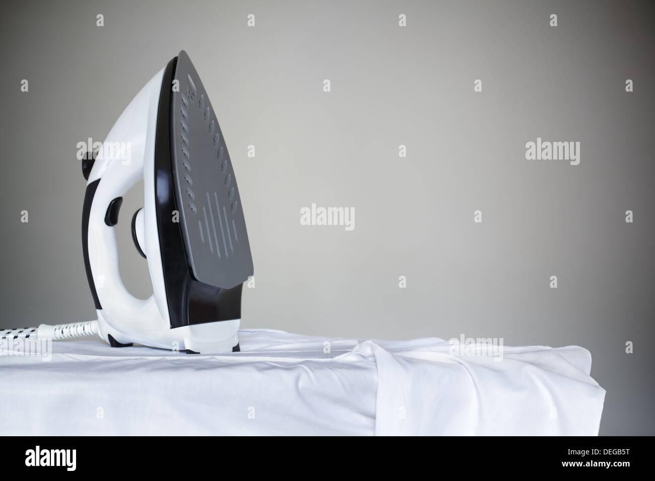 Iron resting on shirt - Stock Image