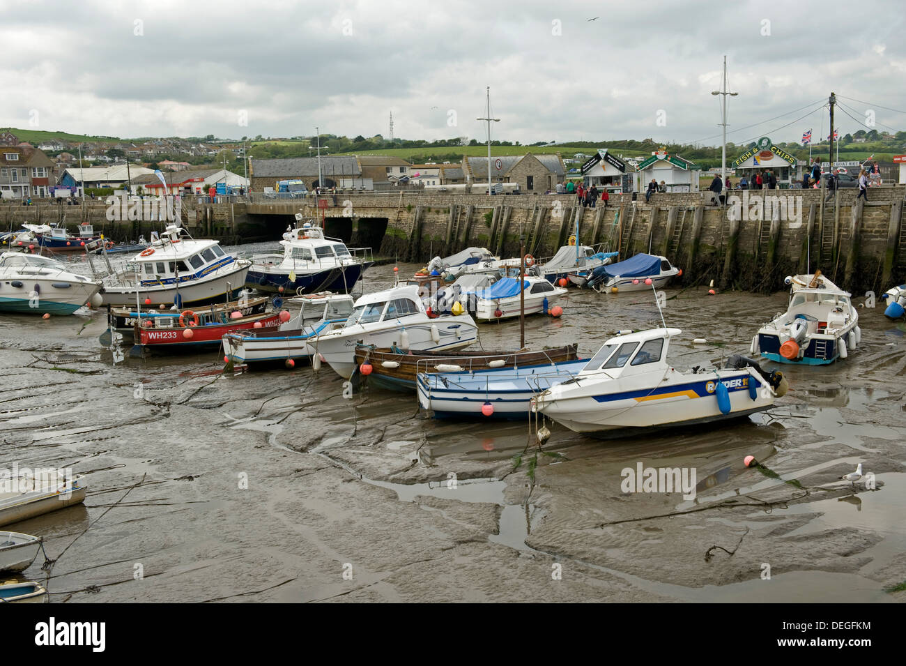 Fishing and leisure boats resting on the mud at low tide in West Bay Harbour, near Bridport in Dorset, May Stock Photo