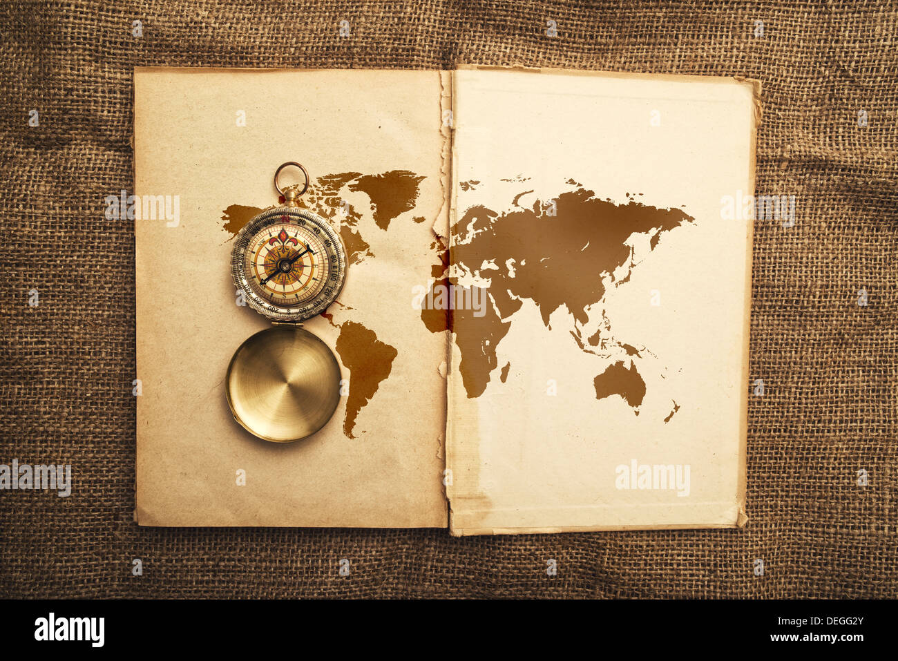 Vintage open book with old navigation compass and world map. - Stock Image