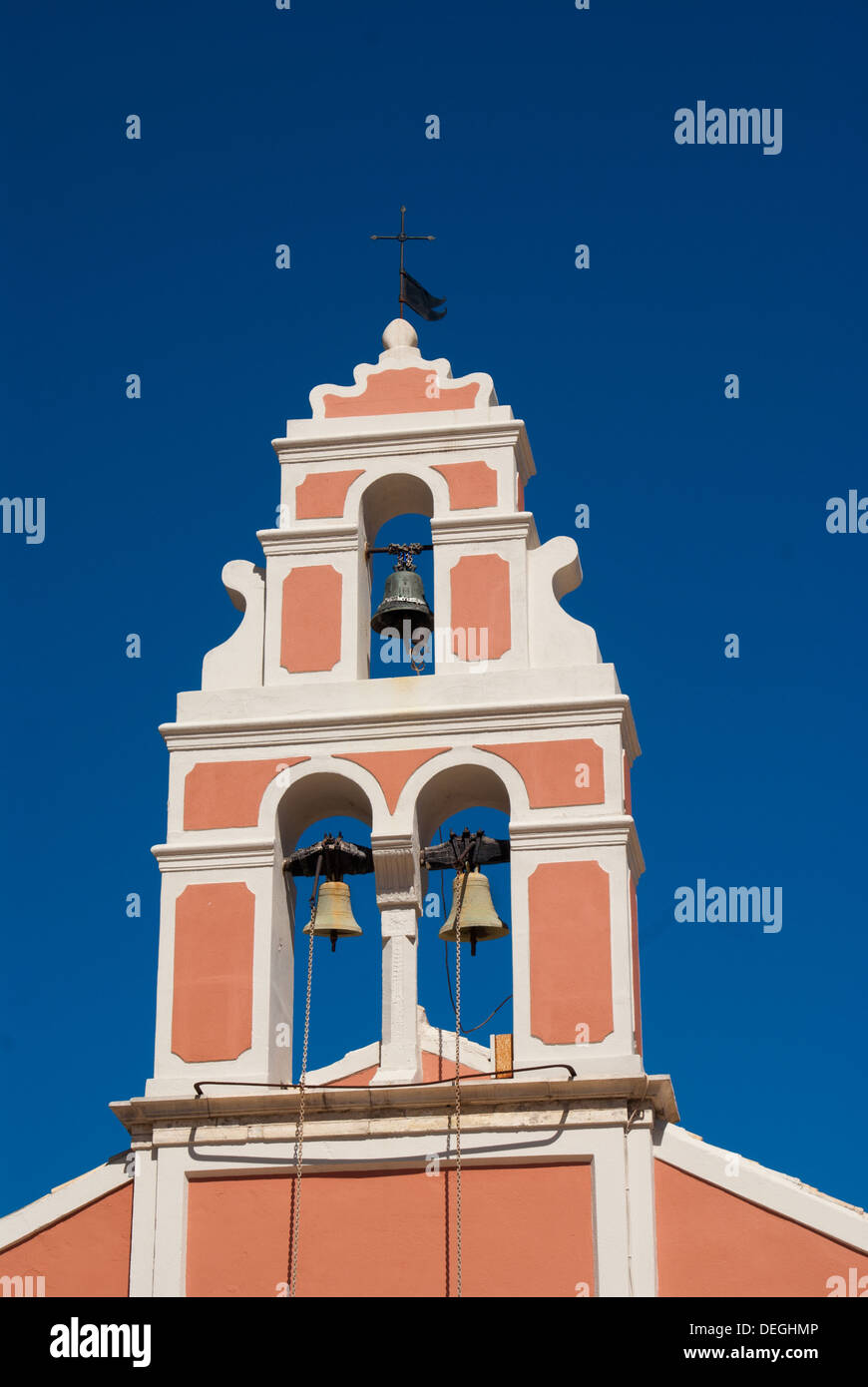 Church bell hanging from arch of bell tower, Fiskardo Kefallonia Greece - Stock Image