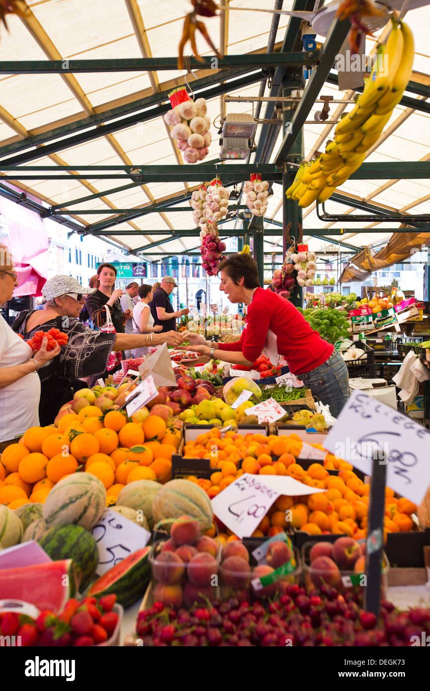 Woman selling fruits at market stall, Tronchetto Mercato, Venice, Veneto, Italy - Stock Image