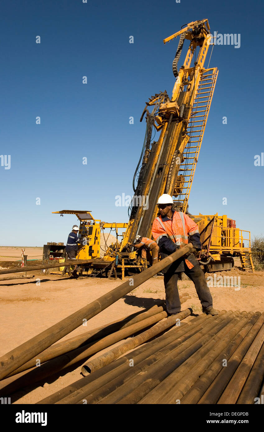 Rig operator pulling out core tube and making a new connection on RC diamond drill exploration rig, surface gold mine Mauritania - Stock Image