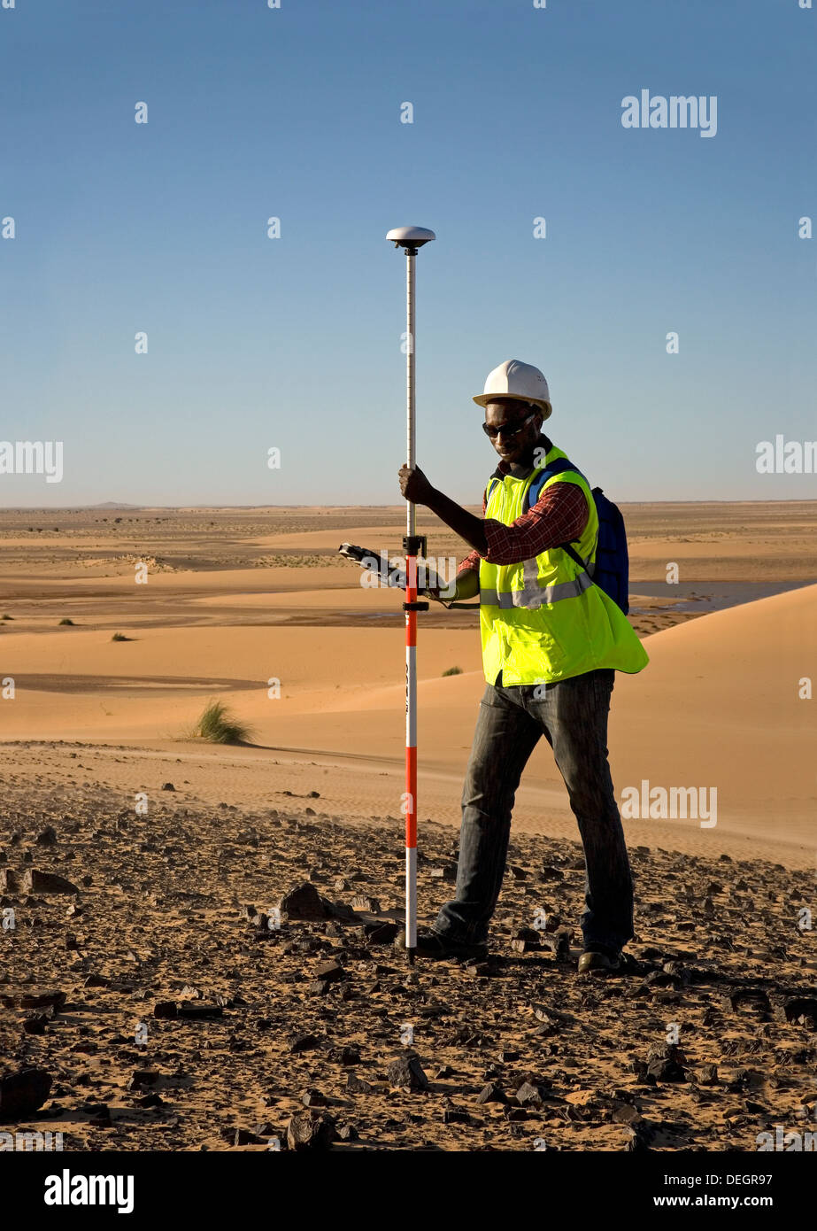 Geological surveyor using differential GPS equipment for a digital terrain survey in the dunes of the Sahara Desert, Mauritania - Stock Image