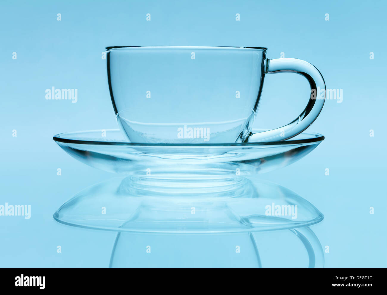 Transparent teacup and saucer over blue background - Stock Image
